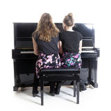 Two teenage girls and black upright piano. In studio against white background royalty free stock photography