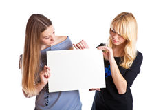 Two teenage girls with card for text Stock Photo