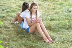 Two teenage girls with cell phones are sitting on  grass Royalty Free Stock Image