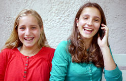 Two teenage girls and cellphone. Two young teenage sisters, one making a phone call Royalty Free Stock Images