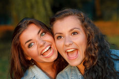 Two teenage girls. Close-up portrait of two happy teenage girls outdoors in jeans wear shouting looking away Royalty Free Stock Images