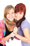 Two teenage girls, friends. Standing on the white background Stock Image
