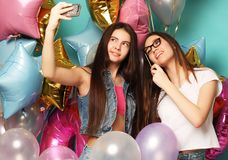 Two teenage girls friends with colorfoul balloons make selfie on a phone. Blue background. Happy time Royalty Free Stock Image