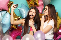 Two teenage girls friends with colorfoul balloons make selfie on a phone. Blue background. Close up Stock Photo