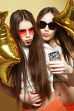 Two teenage girls friends with gold balloons  make selfie on a p Stock Photos