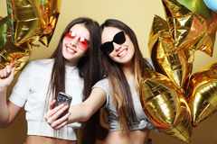 Two teenage girls friends with gold balloons  make selfie on a p Royalty Free Stock Photo