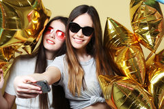 Two teenage girls friends with gold balloons  make selfie on a p Royalty Free Stock Photography