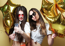 Two teenage girls friends with gold balloons  make selfie on a p Royalty Free Stock Photos
