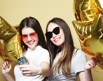 Two teenage girls friends with gold balloons  make selfie on a p Stock Photo