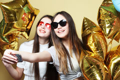 Two teenage girls friends with gold balloons  make selfie on a p Royalty Free Stock Image