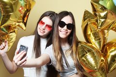 Two teenage girls friends with gold balloons  make selfie on a p Stock Photography
