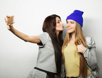 Two teenage girls friends in hipster outfit make selfie Royalty Free Stock Image