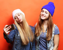 Two teenage girls friends in hipster outfit make selfie on a pho Stock Images