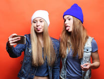 Two teenage girls friends in hipster outfit make selfie on a pho Royalty Free Stock Photography