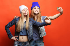 Two teenage girls friends in hipster outfit make selfie on a pho Royalty Free Stock Photo