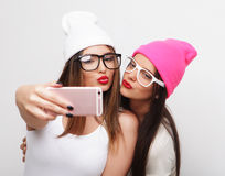 Two teenage girls friends in hipster outfit make selfie Stock Image