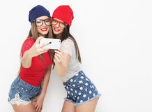 Two teenage girls friends in hipster outfit make selfie Royalty Free Stock Images
