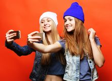 Two teenage girls friends in hipster outfit make selfie on a phone. Two  girls friends in hipster outfit make selfie on a phone. Orange background Royalty Free Stock Images
