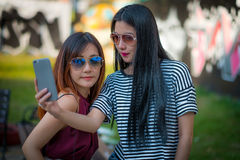 Two teenage girls friends in hipster outfit.at the park outdoors Stock Image