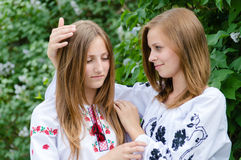 Two teenage girls friends hug of comort. Two young women friends hug for comort outdoors at green tree Royalty Free Stock Photo