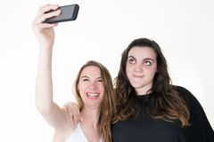 Two teenage girls friends make selfie on a phone. Fit and large body Royalty Free Stock Photos