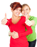 Two teenage girls, friends with thumbs up. White background Royalty Free Stock Photography