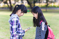 Two teenage girls friends watching the smart phone in school Stock Images