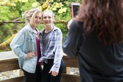 Mom taking photo of girls with mobile phone royalty free stock photo