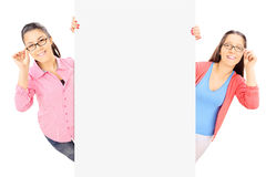 Two teenage girls with glasses standing behind blank panel Royalty Free Stock Images
