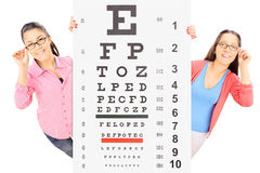Two teenage girls with glasses standing behind an eyesight test Royalty Free Stock Photos