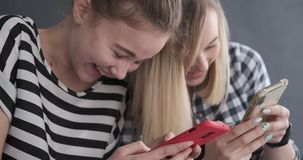 Two teenage girls gossiping while using mobile phones