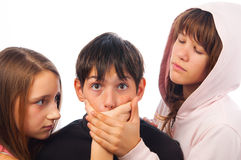 Two teenage girls harassing frightened boy Royalty Free Stock Photo