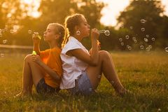 Two teenage girls. Have fun in the park. Two friends outdoor. Summer people doing  bubbles Royalty Free Stock Image