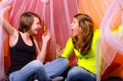 Two teenage girls having fun on the bed. Two teenage girls having fun while sitting on the bed Stock Photos