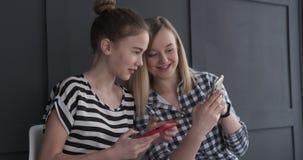 Teenage girls using mobile phones. Two teenage girls having fun playing game on mobile phones stock footage