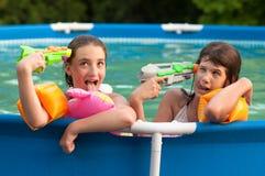 Two teenage girls having fun in the pool Stock Photos