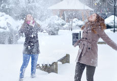 Two teenage girls having fun in the snow in winter. Two teenage girls having fun in the snow on beautiful winter day Royalty Free Stock Images
