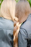 Two teenage girls having their long hair twisted Stock Photo