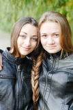 Two teenage girls having their long hair twisted Royalty Free Stock Photos