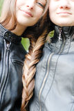 Two teenage girls having their long hair twisted Royalty Free Stock Images