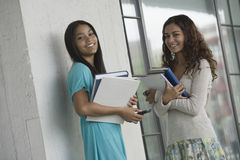 Two teenage girls holding books. Stock Photos