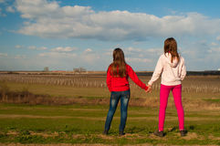 Two teenage girls holding hands in the nature. Two teenage girls standing and holding hands while watching the nature on beautiful sunny spring day stock images