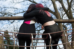 Two Teenage Girls Hugging on Outdoor Playground Royalty Free Stock Images