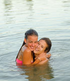 Two teenage girls hugging in the river Stock Image