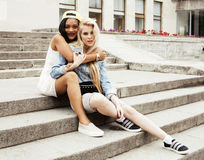 Two teenage girls infront of university building smiling, having Stock Photo