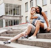 Two teenage girls infront of university building smiling, having Stock Photography