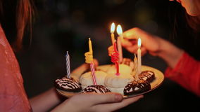 Two teenage girls lighting candles on birthday. Cake with candles close-up. Two teenage girls lighting candles on birthday. Cake with candles close-up Shot in stock video footage