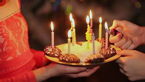 Two teenage girls lighting candles on birthday. Cake with candles close-up stock video