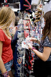 Two teenage girls looking at postcards in a souvenir shop Royalty Free Stock Photo