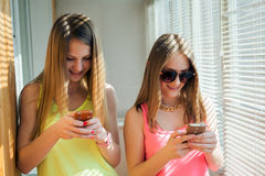 Two teenage girls looking in their gadgets Royalty Free Stock Images